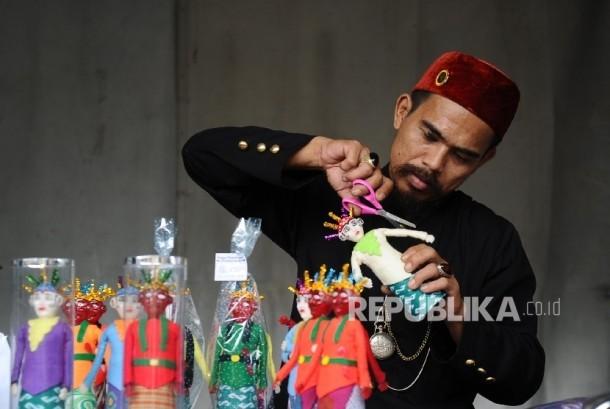 Pengrajin menyelesaikan pembuatan boneka ondel-ondel saat di gelar bazar UMKM di stasiun Gambir, Jakarta, Rabu (28\12).