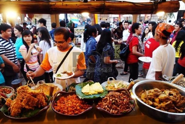 Pengunjung mencicipi salah satu makanan di kedai Jakarta Fashion & Food Festival yang rutin diselenggarakan tiap tahun di Kelapa Gading.