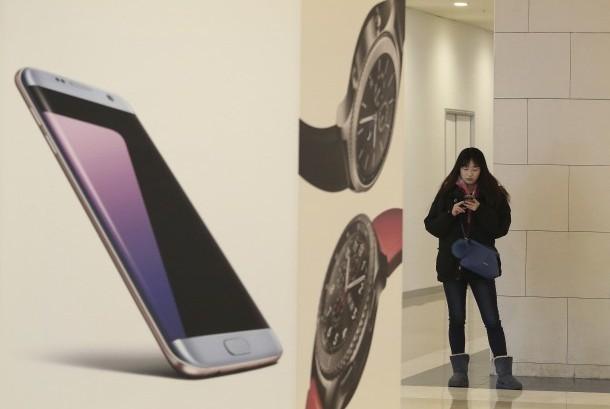 Pengunjung sedang menggunakan posel pintar di samping iklan produk Samsung disala satu pertokoan di Korea Selatan