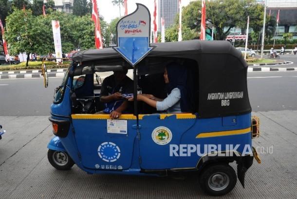 Penumpang menaiki bajaj gas seusai pelepasan 700 bajaj gas gratis di Mobile Refueling Unit (MRU) PGN Station IRTI Monas, Jakarta, Ahad (14/8).
