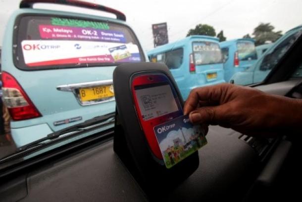 Penumpang menempelkan kartu Ok-Otrip saat menaiki angkutan umum jurusan Kampung Melayu-Duren Sawit di Terminal Kampung Melayu, Jakarta, Senin (15/1).