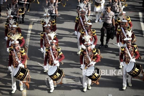 Pertunjukan marching band oleh taruna akademi kepolisian Cendrawasih saat mengikuti kirab 190 bendera negara peserta Sidang Umum Interpol ke-85 saat berlangsungnya hari bebas kendaraan bermotor di Jakarta, Ahad (29/10).