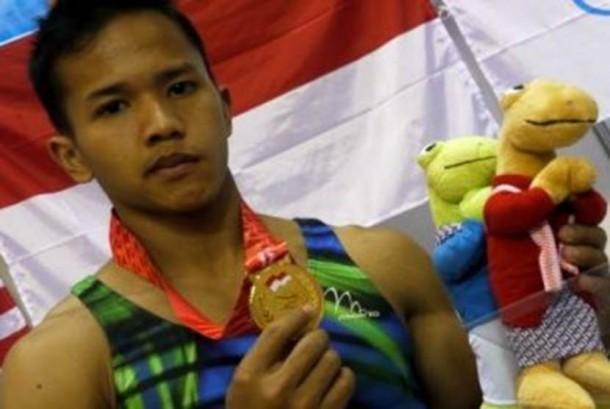 Pesenam Indonesia, Muhammad Try Saputra menunjukkn medali emas yang diperoleh dari final senam artistik final perorangan alat palang tunggal SEA Games XXVI di GOR Ranau, Jakabaring Sport Center (JSC), Palembang, Sumsel, Selasa (15/11).