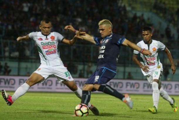Pesepak bola Arema FC Cristian Gonzales (tengah) berusaha melewati hadangan pesepak bola PS TNI Safri Al Irfandi (kiri) dan Izmy Yaman Hatuwe (kanan) dalam pertandingan Liga I GOJEK-Traveloka di Stadion Kanjuruhan, Malang, Jawa Timur, Sabtu (14/10).