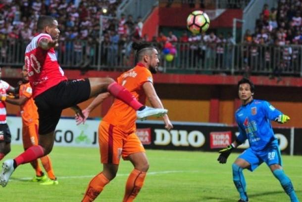 Pesepak bola Madura United (MU) Thiago Fortouso (kiri) berusaha menendang bola namun dihalangi pemain Pusamania Borneo FC (PBFC) Yamashita Kunohiro (tengah) dalam lanjutan kompetisi Gojek Traveloka Liga 1 di Stadion Gelora Ratu Pamelingan (SGRP) Pamekasan, Jawa Timur, Jumat (13/10) malam. Pertandingan berakhir imbang 1-1.