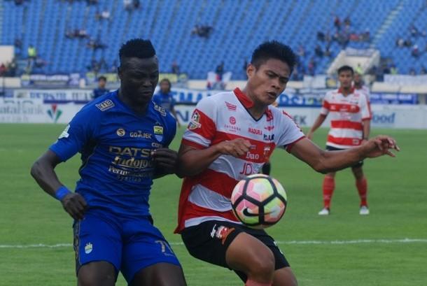 Pesepak bola Persib Bandung Ezechiel Ndouasel (kiri) berebut bola dengan pesepak bola Madura United FC Fachrudin Wahyudi Aryanto (kanan) pada laga lanjutan GO-JEK Traveloka Liga 1 di Stadion Si Jalak Harupat Soreang, Kabupaten Bandung, Jawa Barat, Kamis (19/10).