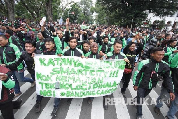 Peserta aksi membawa berbagai poster dan spanduk pada aksi ribuan pengemudi transportasi berbasis aplikasi online di depan Gedung Sate, Kota Bandung, Senin (16/10).