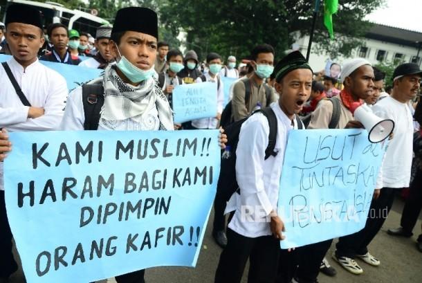 Peserta aksi membentangkan poster di depan Gedung Sate, Kota Bandung, pada Aksi demonstrasi umat Islam terkait pernyataan kontoversi Gubernur DKI Jakarta, Basuki Tjahaja Purnama atau Ahok yang mengutip salah satu ayat Alquran, Jumat (21/10).