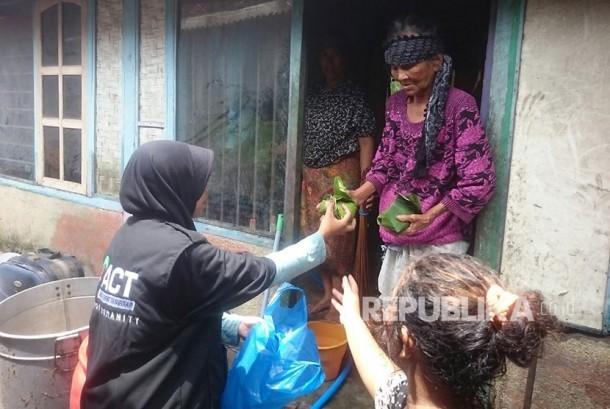 Petugas ACT sedang memberikan bantuan bagi korban banjir