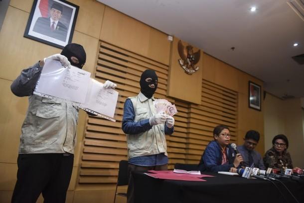 Petugas KPK menunjukkan barang bukti uang Dolar Singapura dan bukti transfer disaksikan dua pimpinan KPK saat konferensi pers terkait operasi tangkap tangan di Gedung KPK, Jakarta, Rabu (29/6). (Antara/Hafidz Mubarak A)