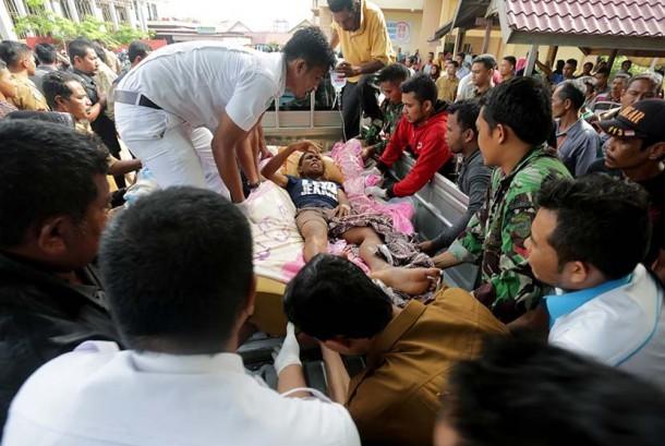 Petugas medis dibantu warga dan prajurit TNI berusaha mengangkat seorang korban gempa saat tiba di Rumah Sakit Umum Daerah (RSUD) Tgk Chik Ditiro Sigli di Pidie, Aceh, Rabu (7/12).