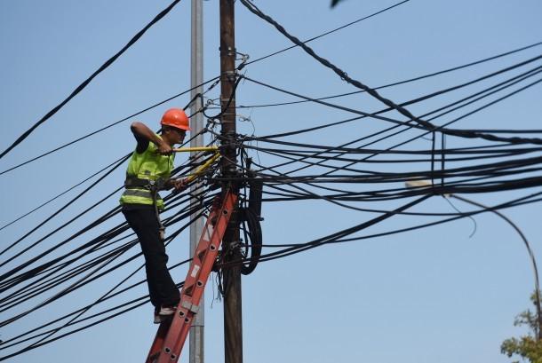 Petugas melakukan pemeriksaan jaringan listrik ilegal pada tiang milik PLN sebelum dilakukan pembokaran di Kawasan Tugu Tani, Jakarta, Jumat (26/2).