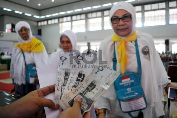 Petugas melakukan pengecekan kembali living cost yang dibagikan kepada calon jamaah haji di Asrama Haji Pondok Gede, Jakarta.
