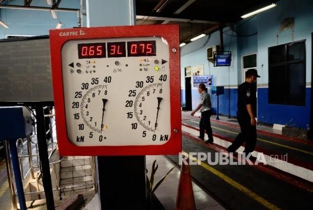 Petugas melakukan pengecekan saat uji uji kendaraan bermotor (KIR) Taksi berbasis aplikasi daring (online) di Pengelola Pengujian Kendaraan Bermotor, Pulo Gadung, Jakarta Timur, Senin (1/8).(Republika/Yasin Habibi)