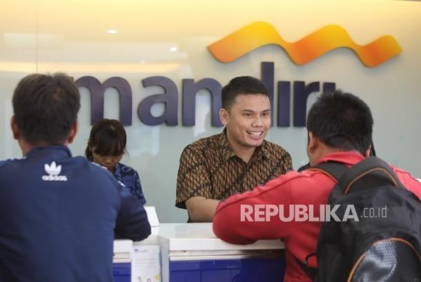 Petugas melayani penyetoran uang oleh nasabah di cabang Bank Mandiri Pertamina UPMS III, Jakarta, Rabu (28/6).