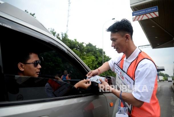 Petugas menawarkan kartu e-toll kepada pengguna jalan tol usai di laksanakanya Launching e-Payment Toll di Pintu Gerbang tol Jati Asih, Jakarta, Senin (21/3). (Republika/Prayogi)