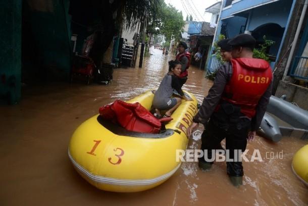 Petugas mengevakuasi warga denga perahu karet saat banjir melanda Kelurahan Cipinang Melayu, Kecamatan Makassar, Jakarta Timur, Senin (20/2).