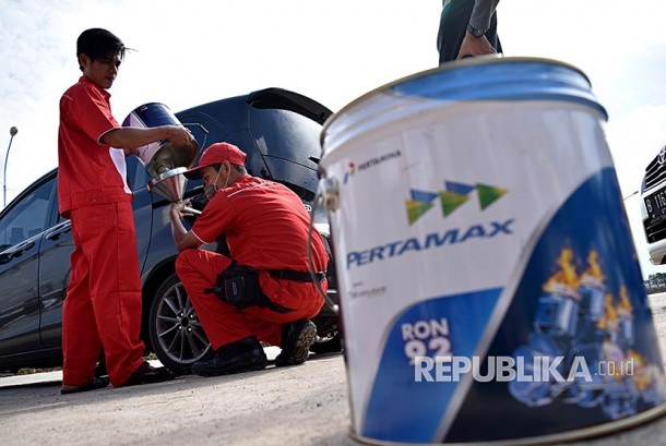 Petugas mengisi BBM jenis Pertamax pada mobil milik pemudik di kios BBM kemasan milik Pertamina.