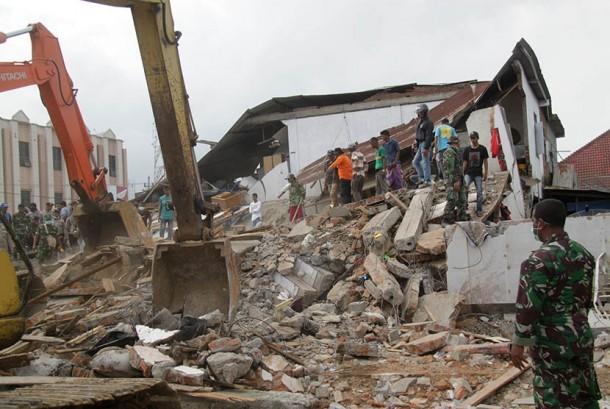 Petugas mengoperasikan alat berat untuk mencari korban yang tertimpa reruntuhan bangunan rumah toko (ruko) akibat gempa di Desa Ulee Glee, Kecamatan Bandar Dua, Kabupaten Pidie Jaya, Aceh, Rabu (7/12).