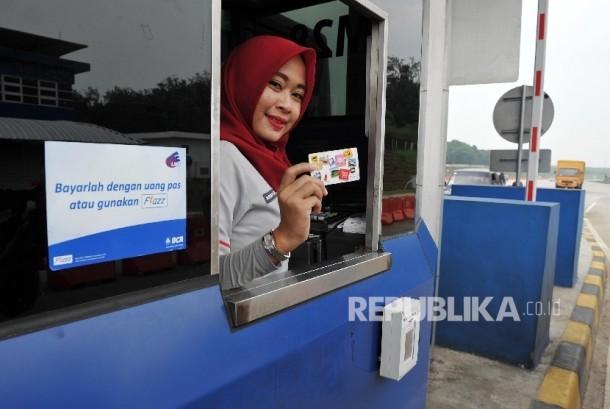 Petugas menunjukkan kartu BCA Flazz di gerbang Tol Cikopo KM 78 Jalan Tol Cikopo – Palimanan (Cipali), Kamis (31/3).