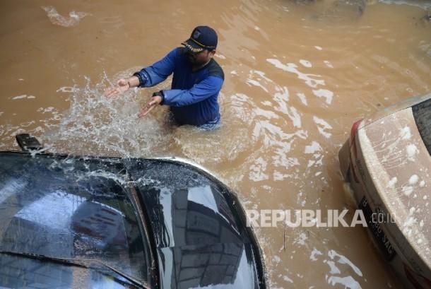 Petugas menyiram kendaraan terjebak banjir di parkir basement di Jalan Kemang Raya, Jakarta, Ahad (28/8)(Republika/Wihdan)