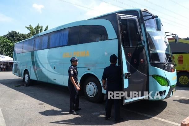 Petugas pemeriksaan kendaraan angkutan darat antar kota antar provinsi (AKAP) di Terminal Kampung Rambutan, Jumat (24/6). (Republika/ Yasin Habibi)