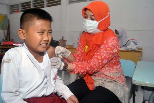 Petugas Puskesmas Sindangbarang Bogor memberikan imunisasi campak Rubella kepada siswa di SD Insan Kamil, Kota Bogor, Jawa Barat, Rabu (9/8).