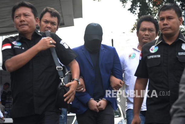 Petugas Sat Res Narkoba Polres Jakarta Barat membawa penyanyi dangdut Ridho Rhoma saat menjalani pemeriksaan di Balai Laboratorium Narkoba BNN, Jakarta, Senin (27/3).