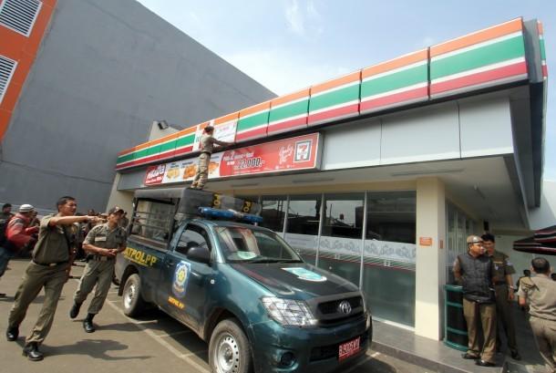 Petugas Satpol PP Tangsel melakukan penyegelan mini market Seven Eleven di kawasan Gaplek, Pamulang, Tangerang Selatan, Selasa (23/7).