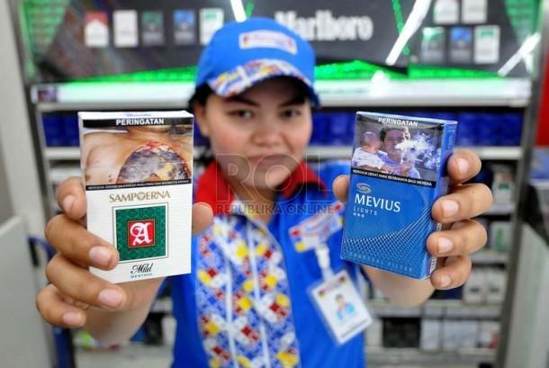Petugas supermarket menunjukan sejumlah rokok yang sudah dilengkapi peringatan bergambar akan bahaya merokok di Jakarta, Senin (23/6).