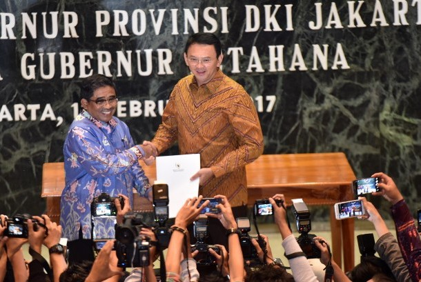 Plt Gubernur DKI Jakarta Soni Sumarsono (kiri) menyerahkan laporan nota singkat kepada Gubernur Petahana Basuki Tjahaja Purnama di Balai Kota Jakarta, Sabtu (11/2).