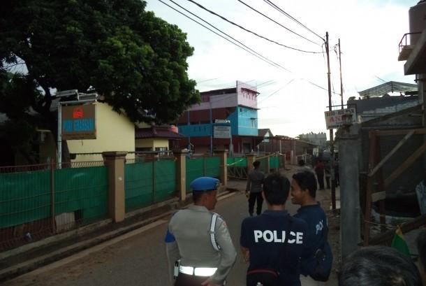 Polisi berjaga di lokasi penggerebakan sebuah rumah di Bintara Jaya, Bekasi, Sabtu (10/12). Di rumah bertingkat tiga bercat biru dan pink itu ditemukan benda diduga bom.