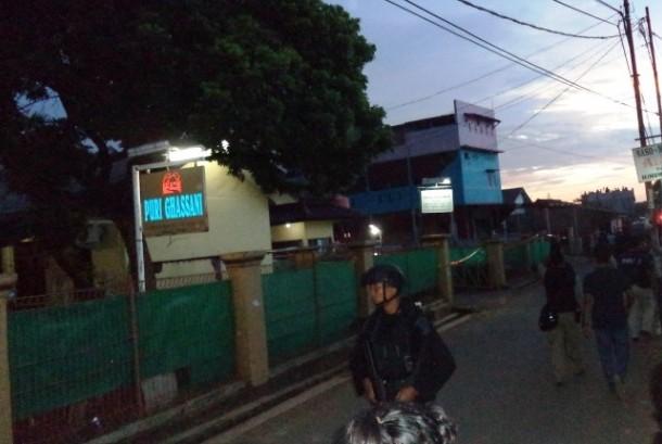 Polisi berjaga di lokasi penggerebakan sebuah rumah di Bintara Jaya, Bekasi, Sabtu (10/12). Di rumah bertingkat tiga bercat biru dan pink ditemukan benda diduga bom.