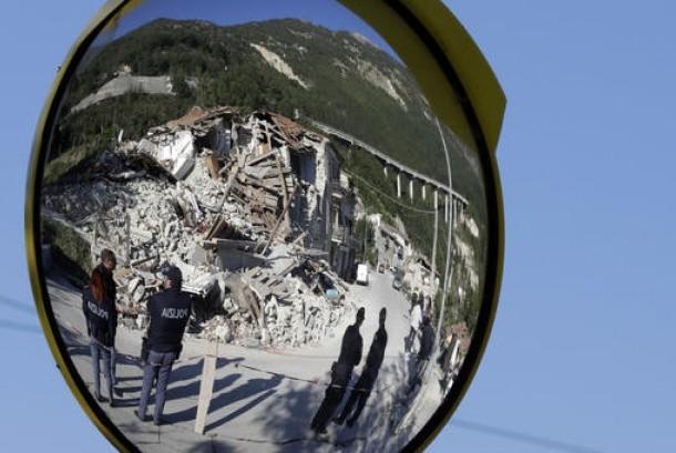 Polisi Italia tampak dari cermin lalu lintas dekat rumah yang hancur akibat gempa bumi di Pescara Del Tronto, Italia, Kamis, 25 Agustus 2016.