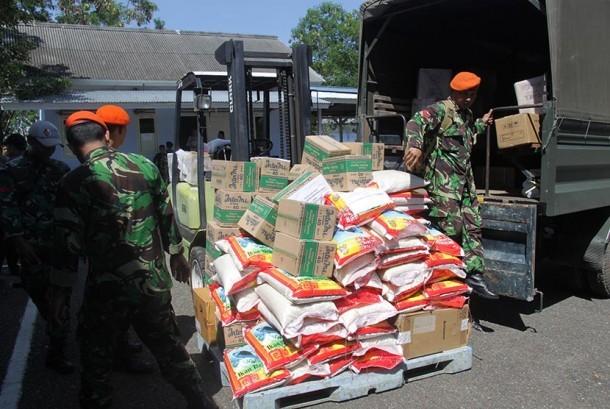 Prajurit TNI membongkar muat logistik bantuan Pemprov Riau dan Pemkot Pekanbaru yang baru tiba di Lanud Sultan Iskandar Muda, Aceh, Besar, Aceh, Kamis (8/12).