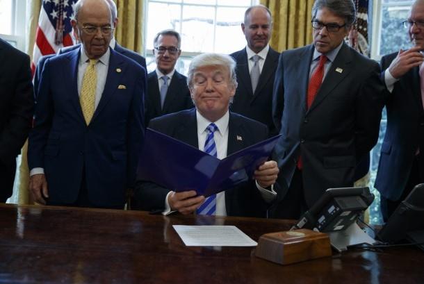 Presiden Donald Trump bersama Menteri Perdagangan Wilbur Ross (kiri) dan Menteri Energi Rick Perry di Oval Office Gedung Putih di Washington.