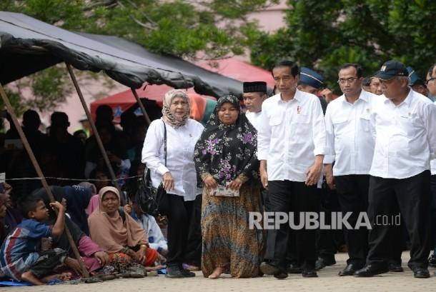 Presiden Joko Widodo bersama pengungsi saat mengunjungi tempat pengungsian korban gempa di Meureudu, Pidie Jaya, NAD, Jumat (9/12).