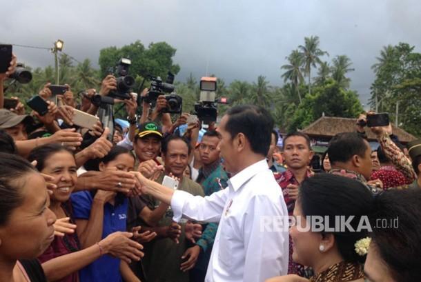 Presiden Joko Widodo (Jokowi) memberikan bantuan kepada para pengungsi erupsi Gunung Agung di lapangan Desa Ulakan, Karangasem, Bali, Selasa (26/9).