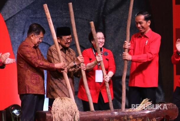 Presiden Joko Widodo (kanan) bersama Wakil Presiden Jusuf Kalla (kiri), Presiden Ke-3 RI BJ Habibie (kedua kiri) dan Ketua Umum PDIP Perjuangan Megawati Soekarnoputri (kedua kanan) menumbuk gabah saat membuka Rapat Koordinasi Nasional (Rakornas) Tiga Pilar Partai Demokrasi Indonesia Perjuangan (PDIP) di Tangerang, Banten, Sabtu (16/12).