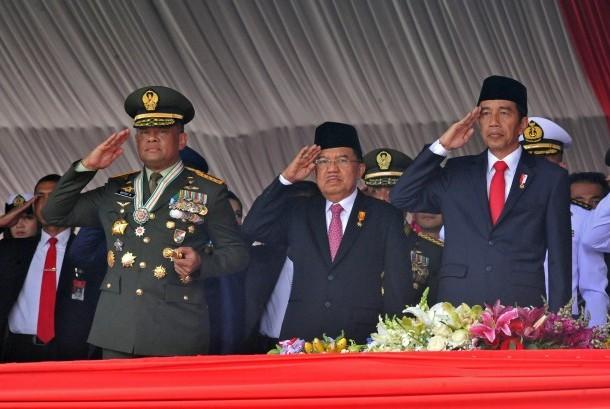 Presiden Joko Widodo (kanan) didampingi Wapres Jusuf Kalla (tengah) dan Panglima TNI Jenderal TNI Gatot Nurmantyo (kiri) memberi hormat pada Upacara Parade dan Defile HUT ke-72 TNI Tahun 2017 di Dermaga Indah Kiat, Cilegon, Banten Kamis (5/10).