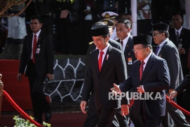 Presiden Republik Indonesia Joko Widodo (kiri) berbincang bersama Wakil Presiden Republik Indonesia Jusuf Kalla (kanan) seusai mengikuti upacara peringatan Hari Kesaktian Pancasila di Monumen Pancasila Sakti, Lubang Buaya, Jakarta, Sabtu (1/10).