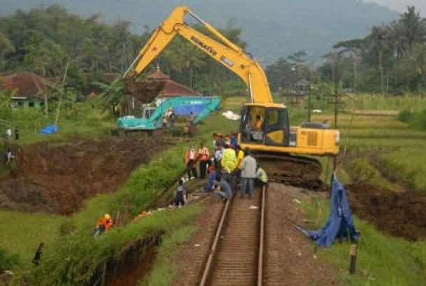 Pekerja menggunakan alat berat memadatkan kembali tanah longsor di perlintasan rel kereta api yang terkena longsor (ilustrasi)