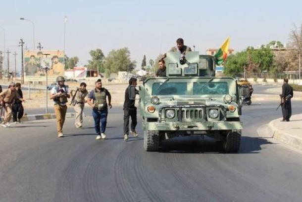 Relawan dan pasukan Peshmerga Kurdi membawa senjata di utara Kirkuk, Irak, Senin (16/10).