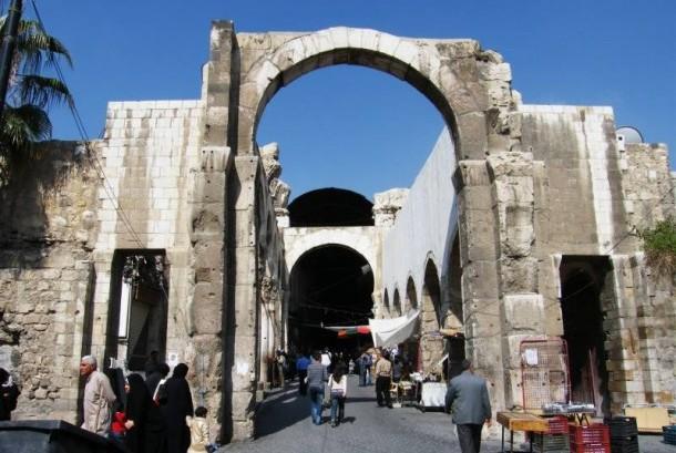 Warga Suriah berjalan di antara puing-puing bangunan setelah serangan udara dari pasukan rezim