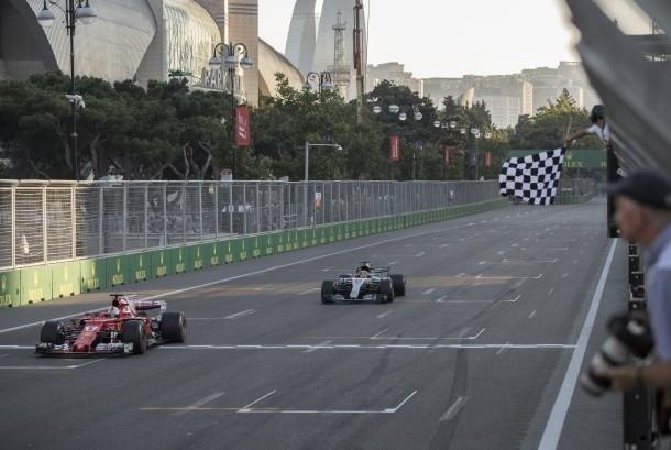 Sebastian Vettel melintasi garis finis GP Azerbaijan di depan Lewis Hamilton, pada Ahad (25/6).