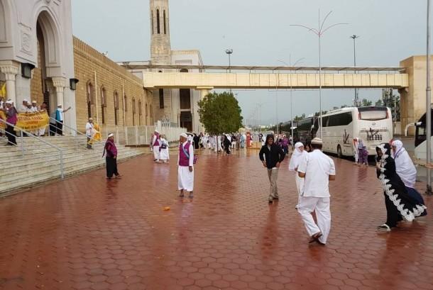 Sejumlah jamaah umrah asal Indonesia menikmati sejuknya jalan-jalan Makkah usai diguyur hujan, Sabtu (29/4).