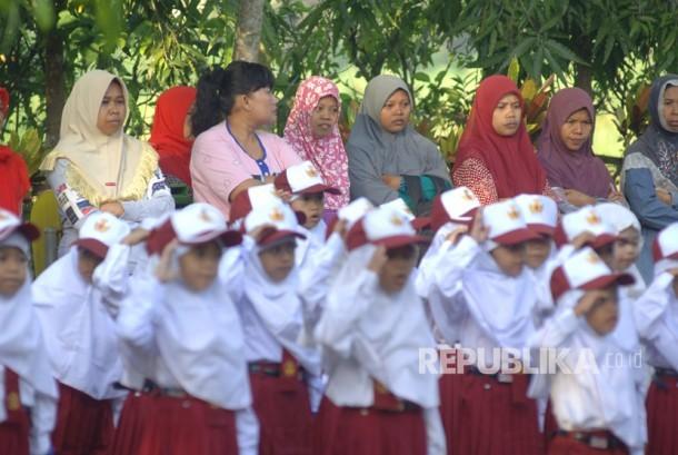 Sejumlah orang tua mendampingi anaknya yang mengikuti upacara bendera di SDN Kowel 3, Pamekasan, Jawa Timur, Senin (17/7).