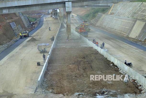 Sejumlah pekerja menyelesaikan proses pembangunan  jalan tol Cisumdawu (Cileunyi-Sumedang-Dawuan) di Kecamatan Rancakalong, Kabupaten Sumedang, Selasa (13/6).