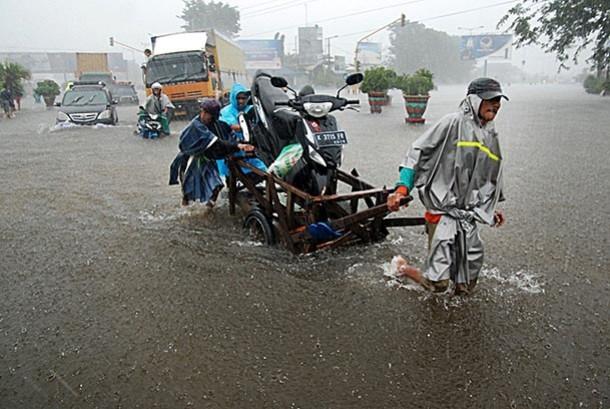 Sejumlah pengguna jalan terjebak banjir di Jalur Pantura Kudus-Pati, Jati, Kudus, Jateng, Selasa (21/1). Untuk kendaraan pribadi jalur Pantura Kudus-Pati dialihkan melalui Jepara dan Demak akibat jalan di sejumlah titik tergenang banjir setinggi 20-100 cm