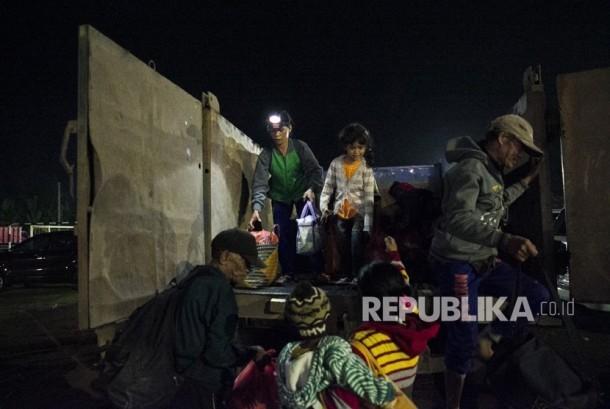Sejumlah pengungsi Gunung Agung turun dari truk setibanya di tempat penampungan GOR Suwecapura, di Klungkung, Bali, Selasa (21/11).